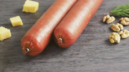 cheese piece : Two sticks of sausage and pieces of cheese and nuts as finished products sausage factory. Stock Footage