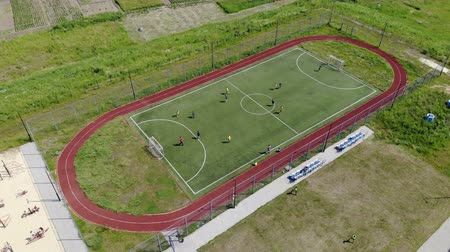 futball labda : Aerial view children play football on a small football field. Modern football ground near the school