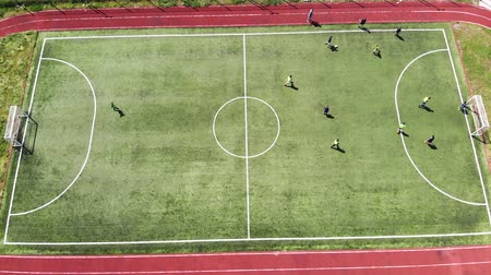 futball labda : Aerial view on top. Children play score a goal by playing football on a small football field. Stock mozgókép