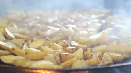 塩辛い : Potatoes close - up which is fried on firewood, covered with smoke. 動画素材