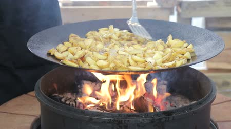 откорме : Cook stirred fried potatoes. Potatoes close - up which is fried on firewood, covered with smoke. Стоковые видеозаписи