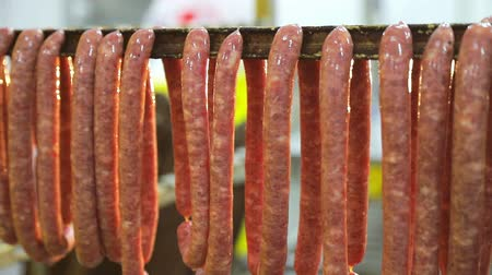 trouba : Production of small hunting sausages of wild boars. Workers strung small sausages on the shelves for further cooking in the oven.