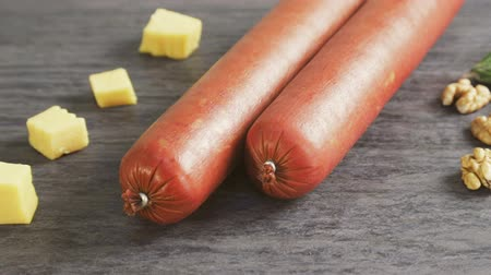 jak : Two sticks of sausage and pieces of cheese and nuts as finished products sausage factory. Dostupné videozáznamy