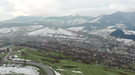 чили : Flying in the mountains in winter in cloudy weather. City in the mountains and green grass Стоковые видеозаписи