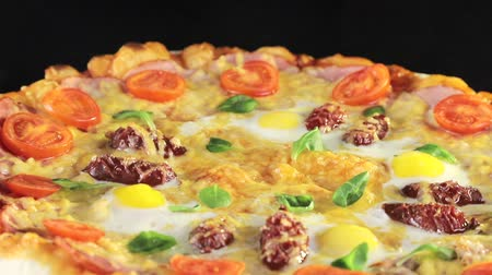 brazilian : close-up of a pizza with cheese tomatoes, sausage and egg that revolves around itself on a black background view from the top