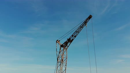 immobilien : Two construction cranes on the background of blue sky and the sun, which shines in the camera hiding behind the construction crane Stockvideo