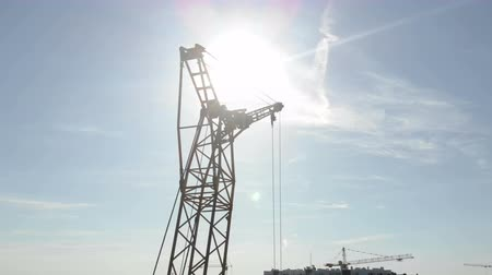 proti : Two construction cranes on the background of blue sky and the sun, which shines in the camera hiding behind the construction crane Dostupné videozáznamy
