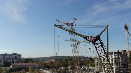immobilien : Construction cranes on the background of the blue sky and the bright sun, which is hidden behind the construction crane