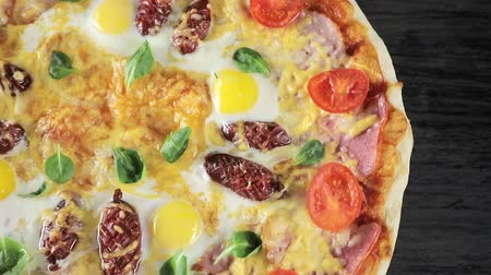 okurka : close-up of a pizza with cheese tomatoes, sausage and egg that revolves around itself on a black background view from the top