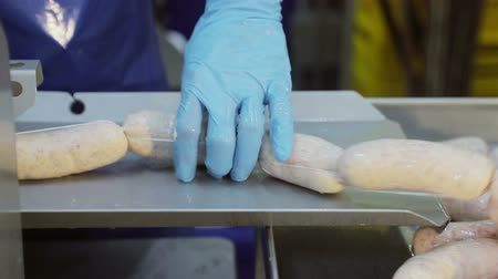 処理された : Sausage production line at the meat processing plant. Employee close-up separates the pieces of sausages with a special device. 動画素材