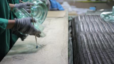 mold : An employee checks the glass insulator of electricity for defects.
