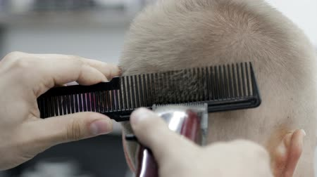 kapster : Stylist hairdresser, using a clipper and comb, cuts her husband close-up.