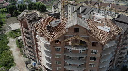 прораб : Aerial Construction of a brick house. Installation of wooden roof Стоковые видеозаписи