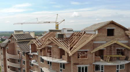 dach : Aerial Construction of a brick house. Installation of wooden roof Wideo