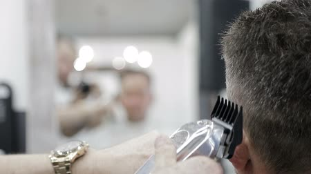 kapster : Mens haircut in Barbershop. Close-up of a master clipping a man with black hair with a clipper.