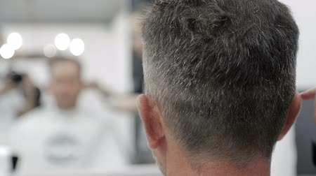 kapster : Herenkapsel in Barbershop. Close-up van een meester die een mens met zwart haar met een clipper knipt. Stockvideo