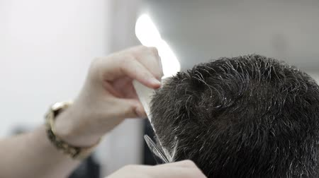 desfocagem : Mens haircut in Barbershop. Close-up of a master cutting a man with black hair with scissors. Stock Footage