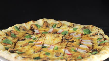 százszorszép : close-up of a pizza with cheese tomatoes, sausage and egg that revolves around itself on a black background view from the top