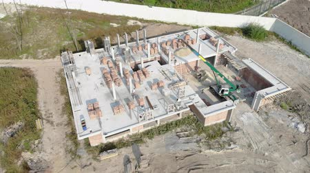 dach : flying over a brick house under construction. Construction workers build a house of brick. New house aerial view