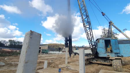 reinforced : Machine drives into the ground piles construction. Construction of the Foundation of reinforced concrete structures.
