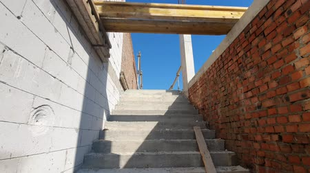 inacabado : Climb the concrete stairs of an unfinished house. Overview of building a house