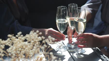флейты : Three Delicate female hands takes a glass of Golden champagne that stands on a table outside on a Sunny day