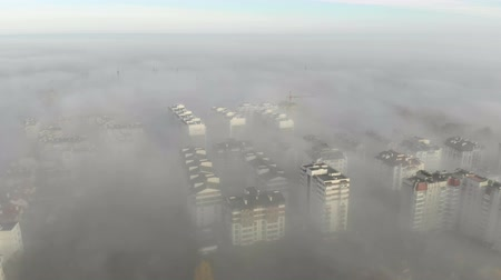 forwards : Aerial view at the houses that are covered with morning fog. Flight over the city of Lviv in Ukraine. Fabulous morning in the fog filmed by drone