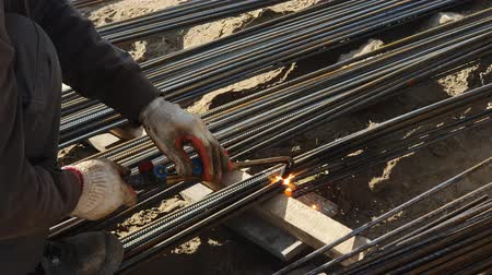 арматура : An employee cuts the rebar at a construction site, using gas welding equipment