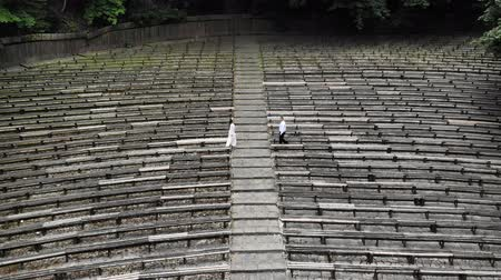 aanpak : Aerial view Two young men in an abandoned Park approach each other and hold hands. An abandoned Park with wooden benches.