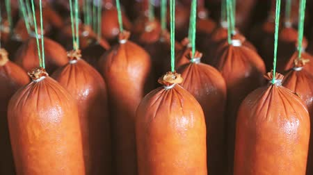 asma : Sausage close - up which is suspended on the shelves, dries in the storage room. Panorama of the sausage which is suspended on laces in the refrigerator.