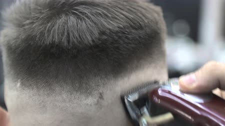 wirtshaus : Barber uses a clipper to cut the clients hair in a chair. Close-up clipper shaves off hair Videos