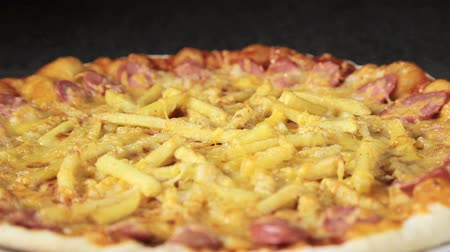 salame : close-up of a pizza with cheese tomatoes, sausage and egg that revolves around itself on a black background view from the top