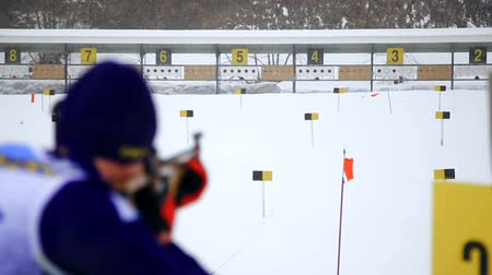 aimed : A skier shoots a rifle at a target. Skier takes part in the biathlon race, standing aimed at the target and made a shot. Stock Footage