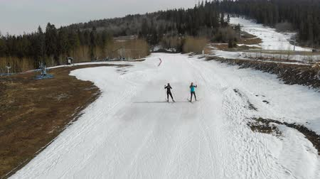 gracefully : Aerial view Two female skiers, walking on skis in a mountainous area. Warm weather and the snow which had melted around Stock Footage