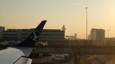 голландский : AMSTERDAM, NETHERLANDS 05 August 2019: Morning sun at Amsterdam airport Schiphol. The plane is taxiing to the runway. View through the plane window of the sunrise at the airport