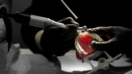 осмотр : Close-up of a dentist practicing on a mock-up of a skeleton of teeth using a drill machine. the dentist deftly practices aligning the front teeth on the layout