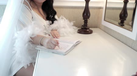 малая глубина резкости : a woman writes a note with a pen, dressed in a white nightgown decorated with feathers