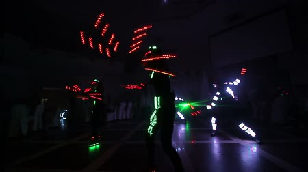 maravilhoso : Laser LED show. Artists demonstrate dance and laser show in a dark room. Clothing glows with ice and laser light. Night laser disco.