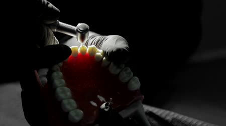 broca : Close-up of a dentist practicing on a mock-up of a skeleton of teeth using a drill machine. the dentist deftly practices aligning the front teeth on the layout