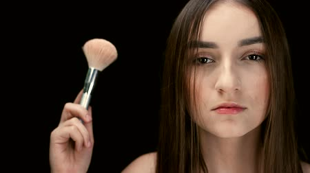 dark eyes : Fashion model girl holds a powder brush in her hand and shakes off the powder. Small particles of powder move in the air.