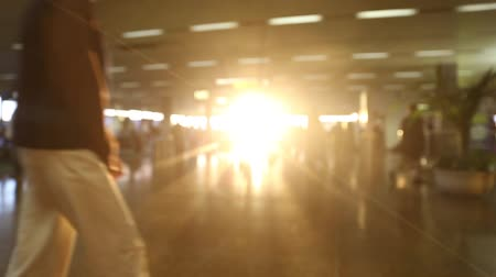 Blurred crowd passing though a beautiful sunlight airport terminal. Stok Video