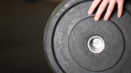 Close up male athlete loads a 45lb weight on a barbell