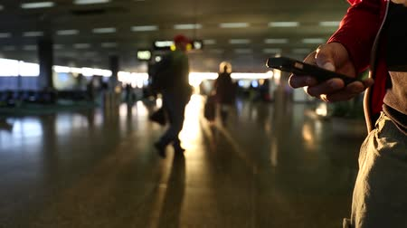 боке : A male navigates his phone with his thumbs with a airport sunset is in the background.