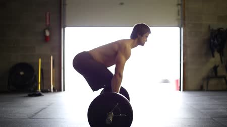 Male Athlete deadlifts a barbell with the light behind him.  Great for a sportshealthfitness promo! Stok Video