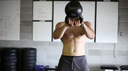Male athlete swinging kettle bell with his shirt off.