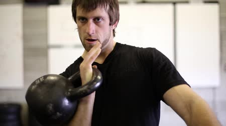 Closeup of a Male cleaning a Kettle bell to his shoulder.  Includes an intense stare at the beginning.