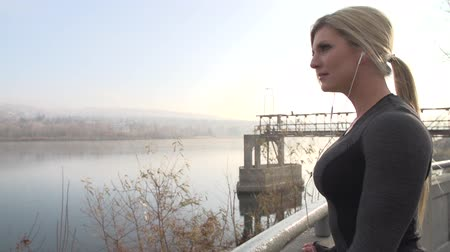 kimerül : Beautiful blonde female stops her run to look out over the river. Stock mozgókép