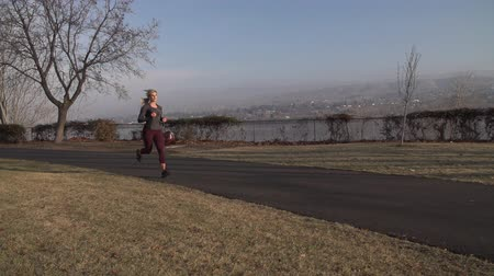 Slow motion clip of female runner running through park.  Shot on a Sony FS700 at 240fps. Stok Video