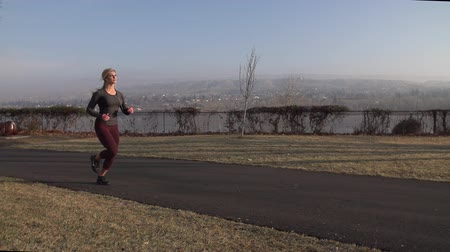 A toned blonde fitness model runs through a park in slow motion with a river as the backdrop. Stok Video