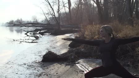 Young beautiful female model does yoga by a river on a cold autumn day.